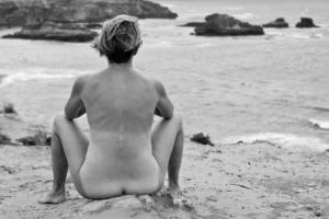nude woman sitting on beach