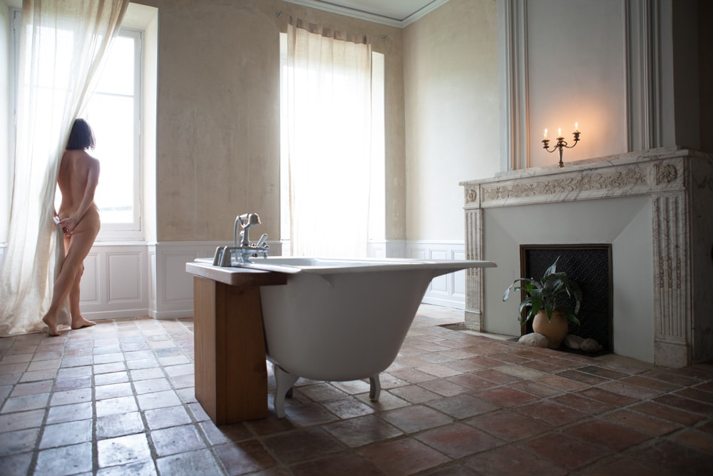 woman in beautiful bathroom, looking out the window.