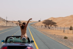 woman standing in car, middle of desert road