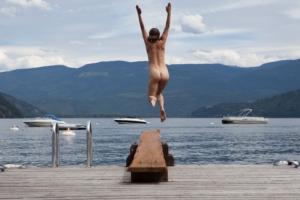 woman jumping in lake