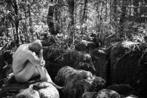 nude man sitting on mossy rock, black and white photo