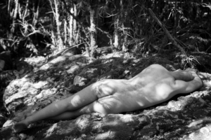 nude man laying in forest, black and white photo
