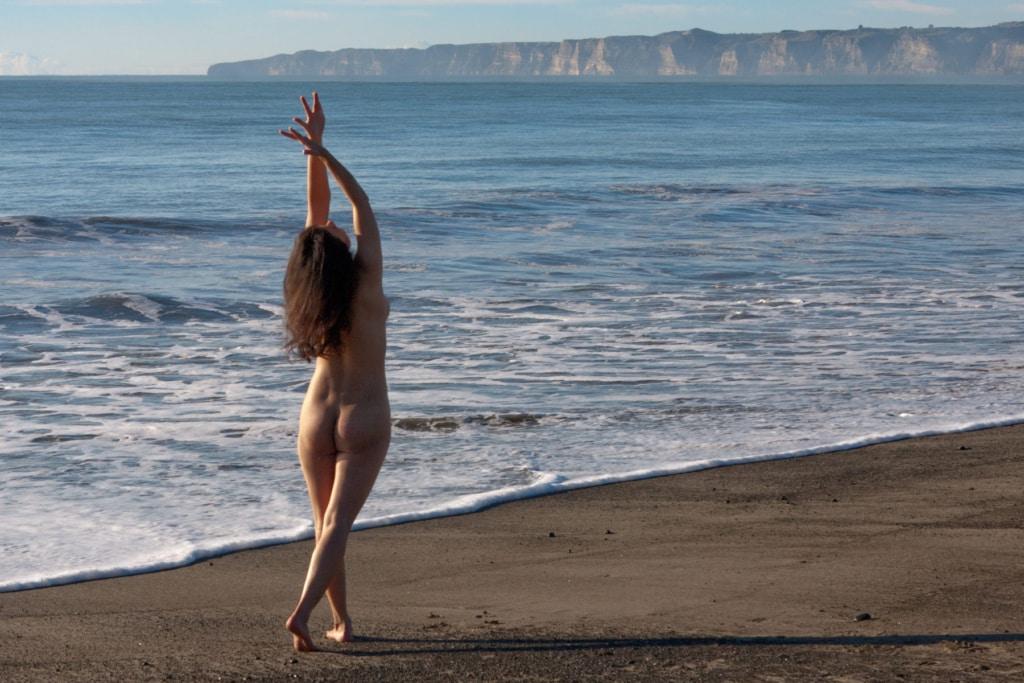 woman standing on beach, long dark hair