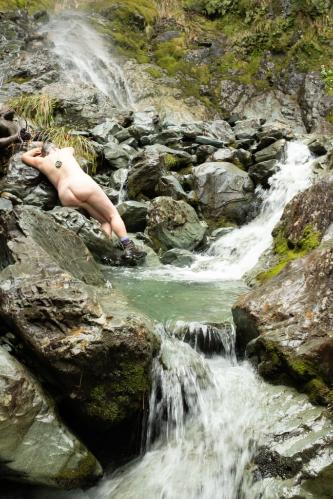 woman laying by a waterfall christine spring photography